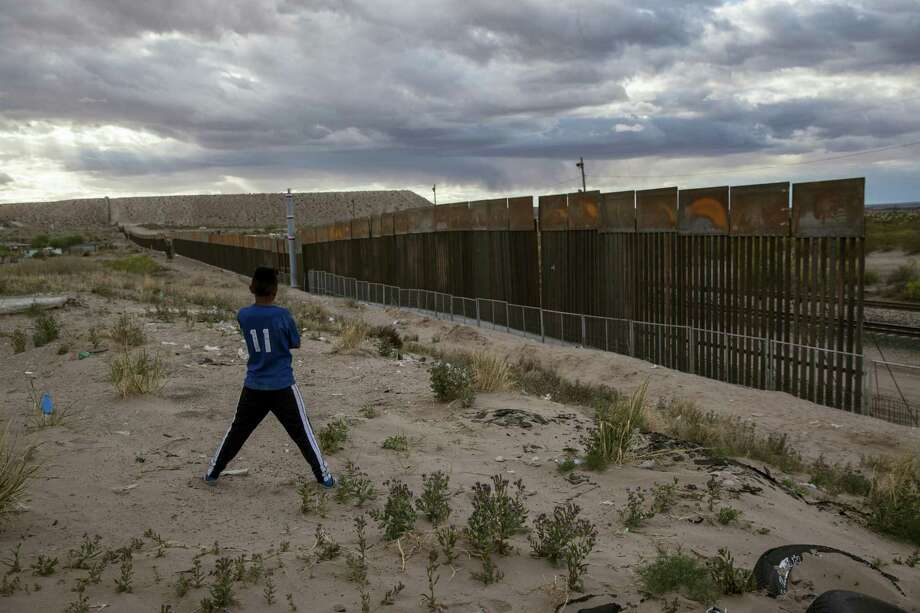 In this March 29, 2017 photo, a youth looks at a new, taller fence being built along U.S.-Mexico border, replacing the shorter, gray metal fence in front of it, in the Anapra neighborhood of Ciudad Juarez, Mexico, across the border from Sunland Park, New Mexico. Most Americans oppose funding President Donald Trump's wall along the U.S.-Mexico border. That's according to a poll released Thursday by The Associated Press-NORC Center for Public Affairs Research. Photo: AP Photo — Rodrigo Abd, File   / Copyright 2017 The Associated Press. All rights reserved.