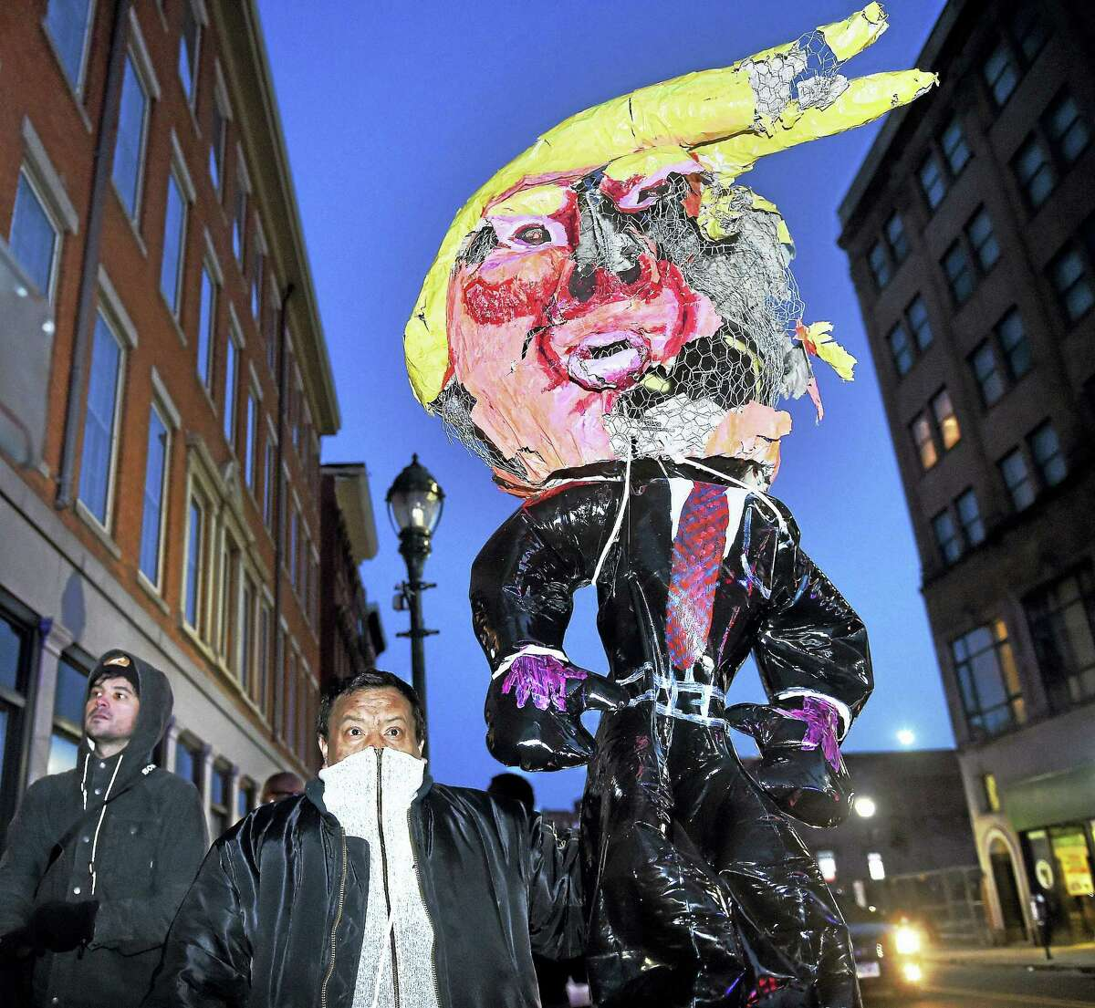 (Arnold Gold-New Haven Register) Edgar Sandoval of New Haven carries an effigy of President Donald Trump during a protest against federal immigration policy on Church St. in New Haven on 2/4/2017. The protest temporarily closed Rt. 34 earlier.