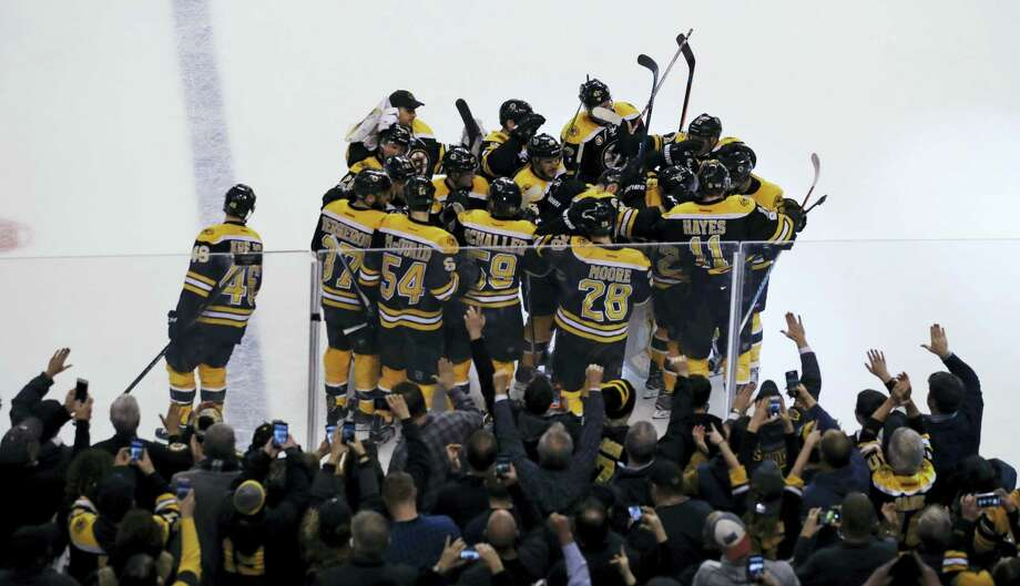 CHARLES KRUPA — THE ASSOCIATED PRESS  Fans celebrate as teammates surround Boston Bruins right wing David Pastrnak after his game-winning goal off Detroit Red Wings goalie Jared Coreau during an overtime period Tuesday. The Bruins defeated the Red Wings 4-3. Photo: AP / Copyright 2017 The Associated Press. All rights reserved.
