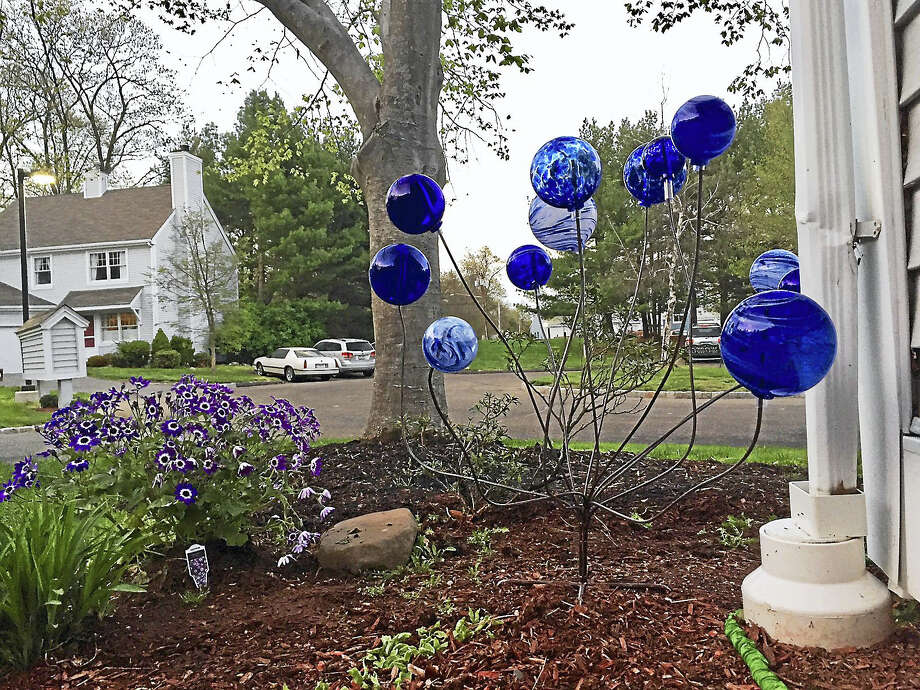 The Art Glass Globe Sculpture floats over wood chips and flowers in the spring. Photo: Joe Amarante — New Haven Register