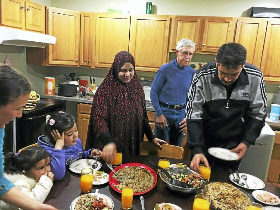 The Almahasnehs serve a meal in their new home to their family and members of their welcome team. Photo: Washington Post Photo By Colby Itkowitz    / The Washington Post