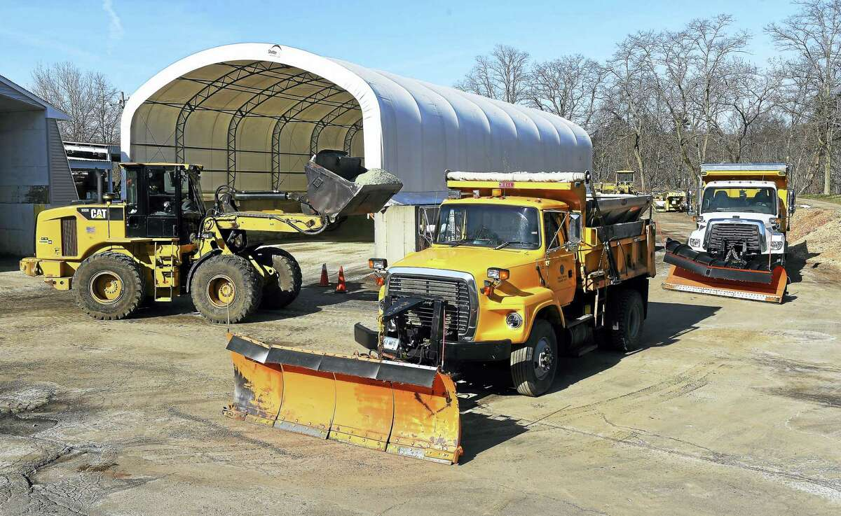 Plows are filled with a molasses/salt mixture at the Milford Public Works Department on Monday to pretreat roads in preparation for the impending snowstorm.