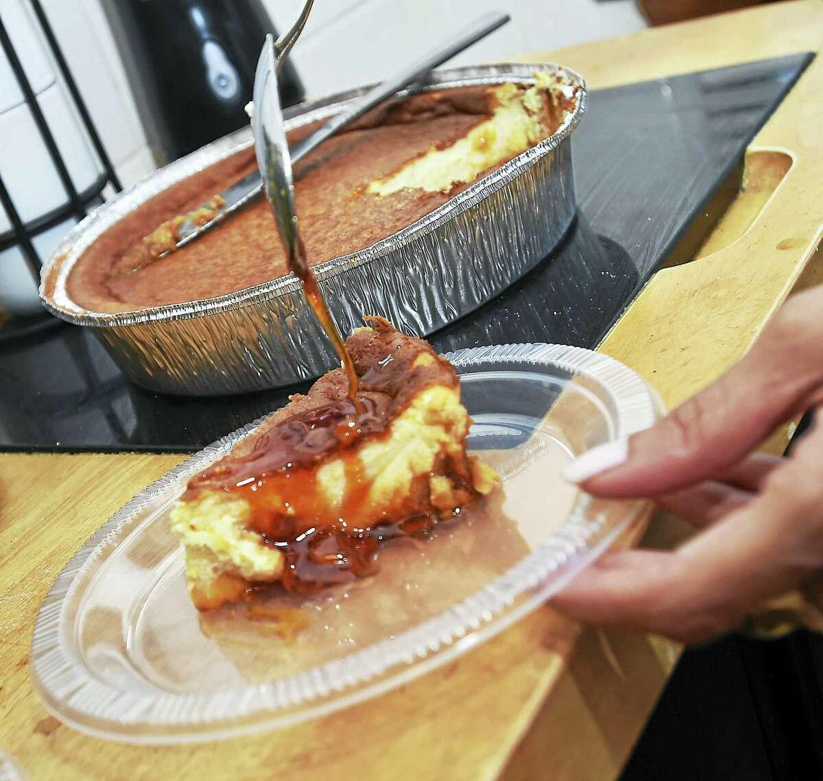 Johanna Torres adds caramelized sugar to a cream cheese flan in her Branford kitchen.