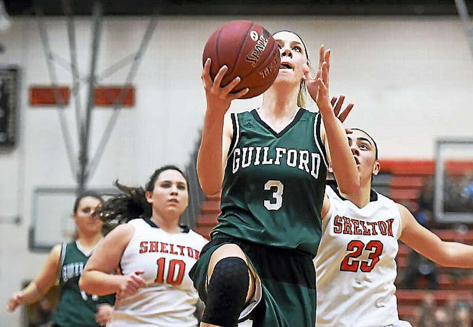 Guilford senior captain Camryn Craig elevates in the paint driving past Shelton junior forward Kayla Resto (23) and senior guard Kathryn Arena in a 63 – 40 win for the Indians at the Vincent J. Murray Memorial Gym at Shelton High School. Photo: Catherine Avalone — New Haven Register
