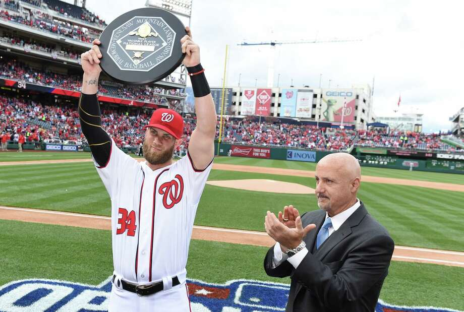 Washington Nationals right fielder Bryce Harper hoists the MVP trophy after it was presented by GM Mike Rizzo last April in Washington. Photo: Washington Post Photo By Jonathan Newton   / The Washington Post