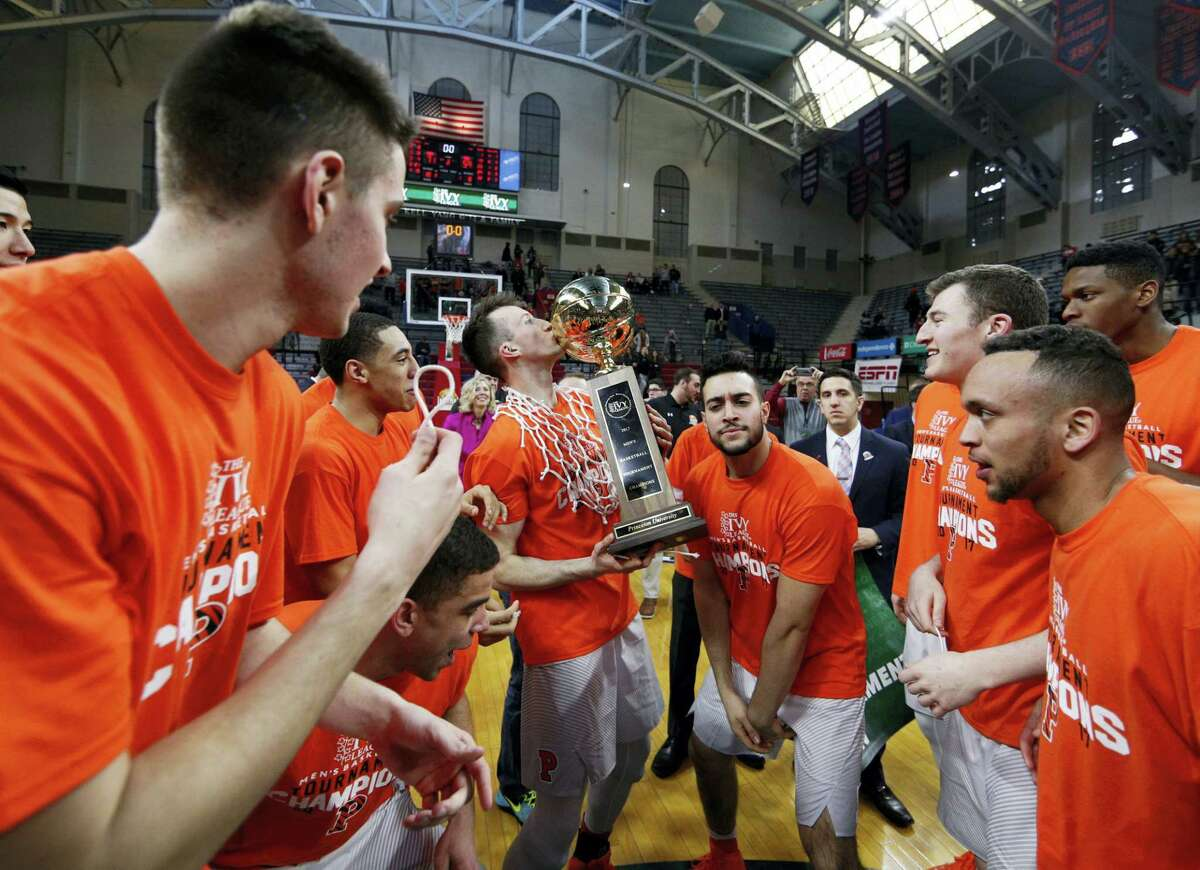 Princeton's Steven Cook, center, kisses the Ivy League Basketball Tournament trophy while surrounded by teammates on Sunday.