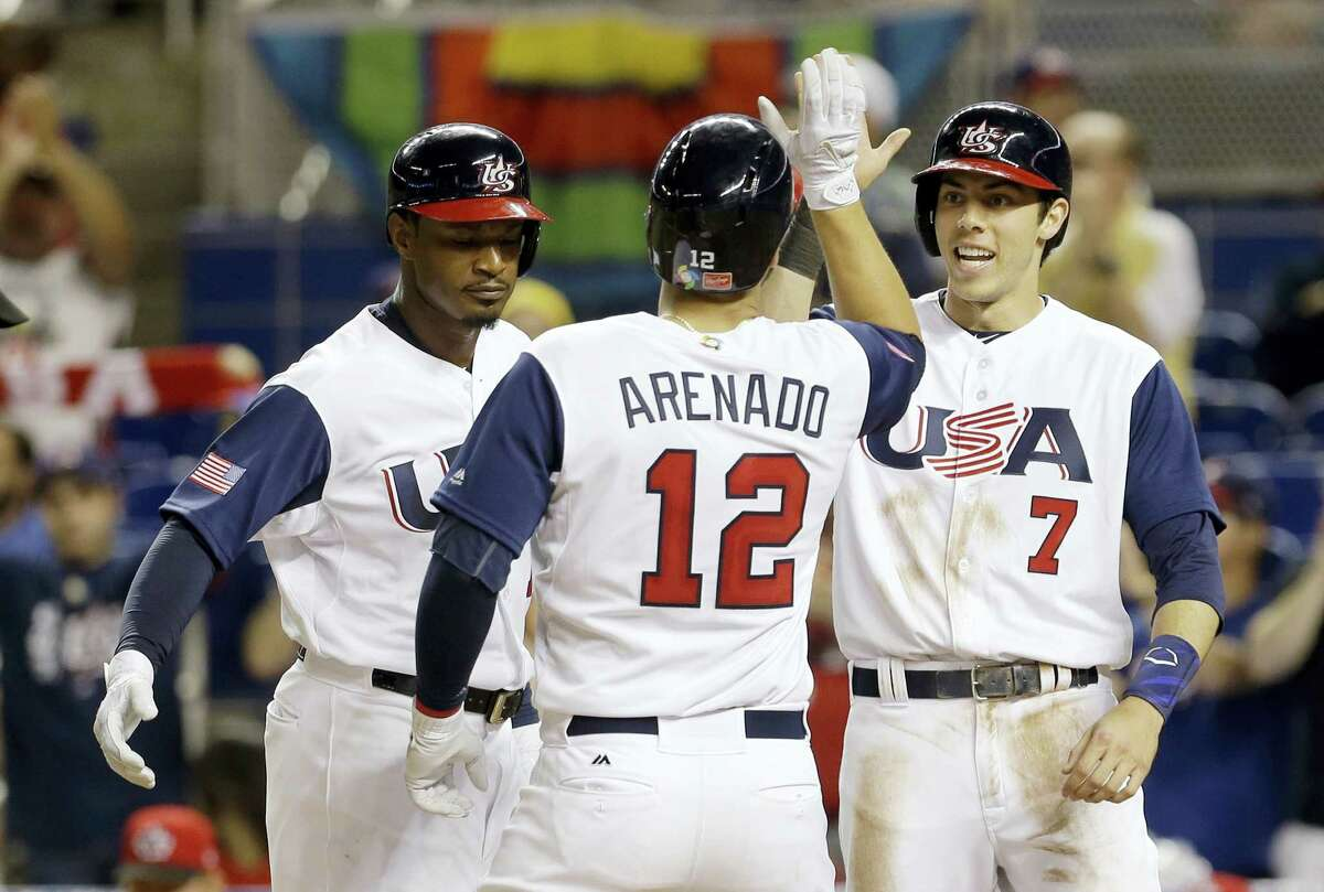 Adam Jones, left, and Christian Yelich (7) congratulate teammate Nolan Arenado after he hit a three-run home run against Canada.