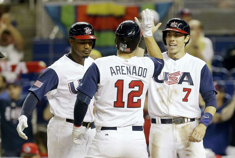 Adam Jones, left, and Christian Yelich (7) congratulate teammate Nolan Arenado after he hit a three-run home run against Canada. Photo: Alan Diaz — The Associated Press   / Copyright 2017 The Associated Press. All rights reserved.