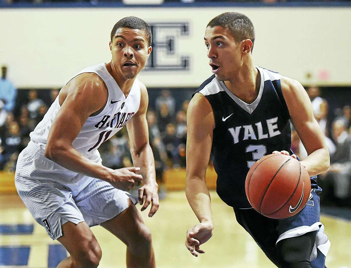 Yale's Alex Copeland drives around Harvard's Bryce Aiken during Saturday's game at the John J. Lee Amphitheater.