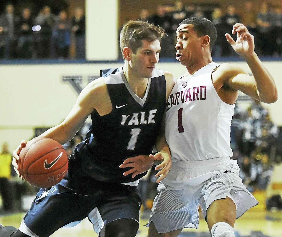 Yale's Anthony Dallier drives the paint as Harvard' Siyani Chambers defends.