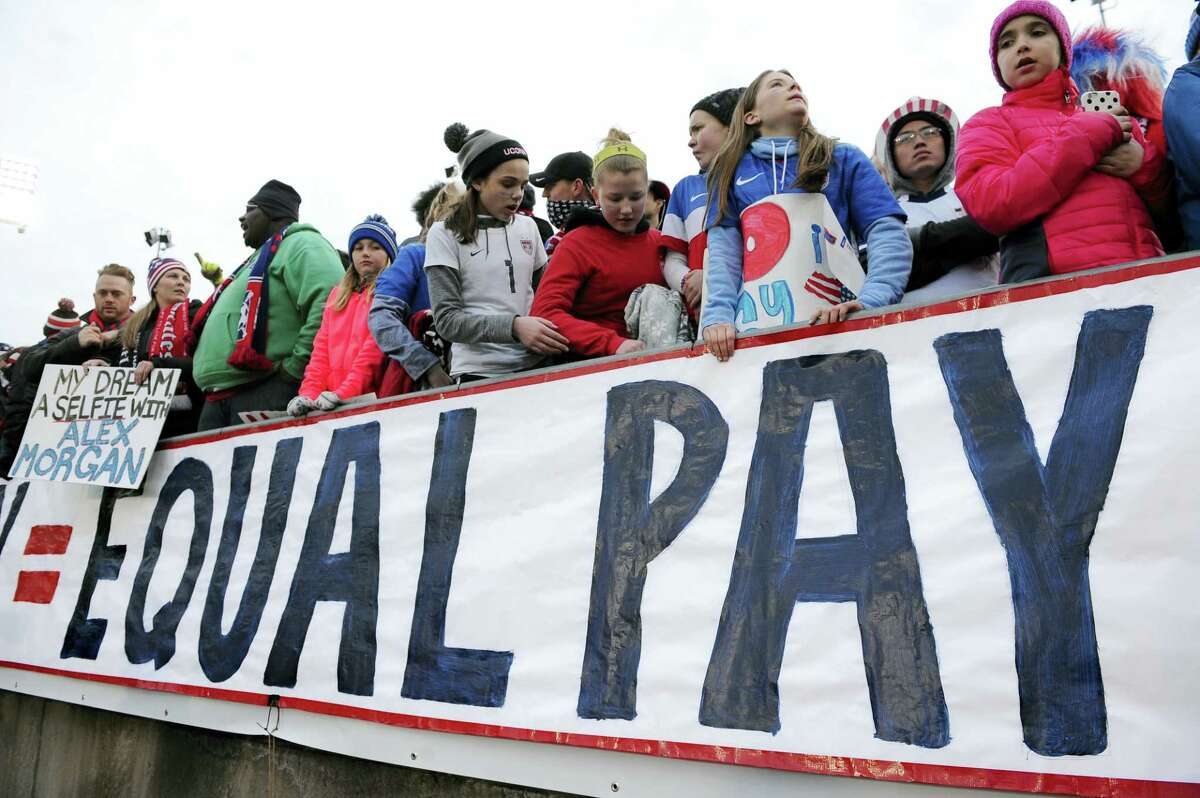In this April 6, 2016 photo, fans stand behind a large sign for equal pay for the women's soccer team during an international friendly soccer match between the United States and Colombia at Pratt & Whitney Stadium at Rentschler Field in East Hartford, Conn. The U.S. Soccer Federation and the World Cup champion women's team have agreed on a labor contract, settling a dispute in which the players sought equitable wages to their male counterparts. The financial terms and length of the multiyear deal were not disclosed. The agreement was ratified by the players and the federation's board on April 4, 2017.