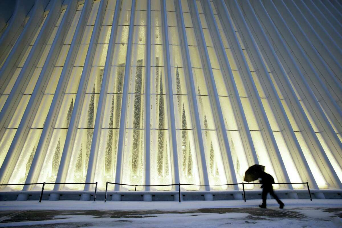 A man makes his way through wind and snow past the Oculus of the World Trade Center Transportation Hub, Thursday, Feb. 9, 2017, in New York. A powerful, fast-moving storm swept through the northeastern U.S. Thursday, making for a slippery morning commute and leaving some residents bracing for blizzard conditions.
