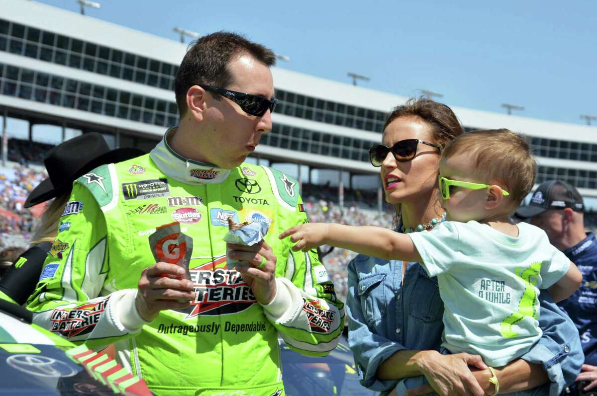 Kyle Busch jokes with his son Brexton, right, as he talks with his wife, Samantha on pit road before a race at Texas Motor Speedway.