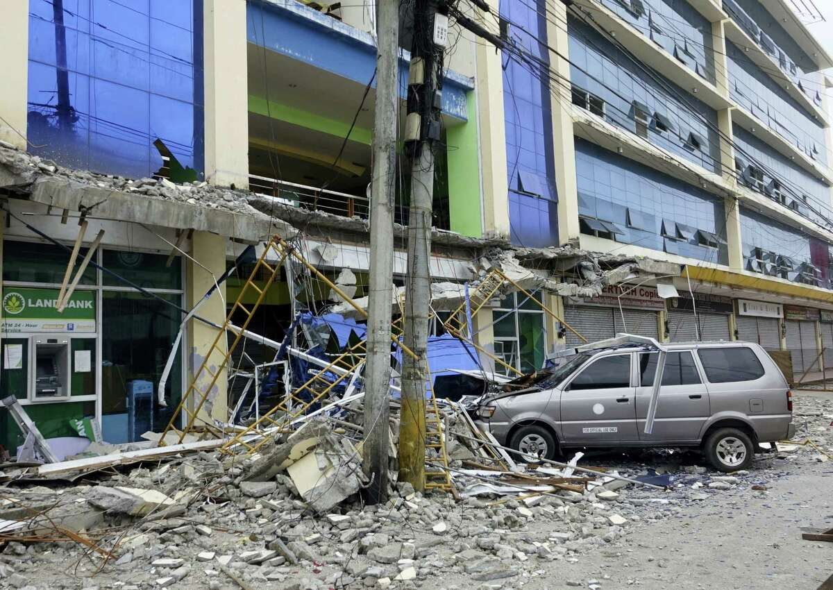 Fallen debris from a building are seen Saturday, Feb. 11, 2017 following a powerful nighttime earthquake that rocked Surigao city, Surigao del Norte province in southern Philippines. The late Friday quake roused residents from sleep in Surigao del Norte province, sending hundreds to flee their homes.