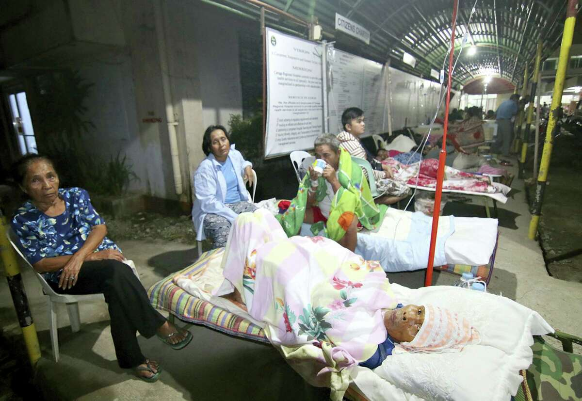 Patients spend the night outside a hospital after abandoning their rooms following a powerful earthquake that rocked Surigao city, Surigao del Norte province, in the southern Philippines, Saturday, Feb.11, 2017. Officials said, the powerful earthquake with a magnitude of 6.5, caused an undetermined number of casualties, damaged roads and buildings, including the airport, and knocked power out.