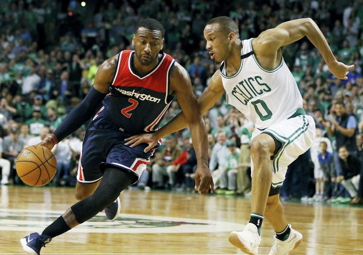 John Wall, left, tries to drive against the Celtics' Avery Bradley during the third quarter of a second-round NBA playoff series basketball game in Boston.