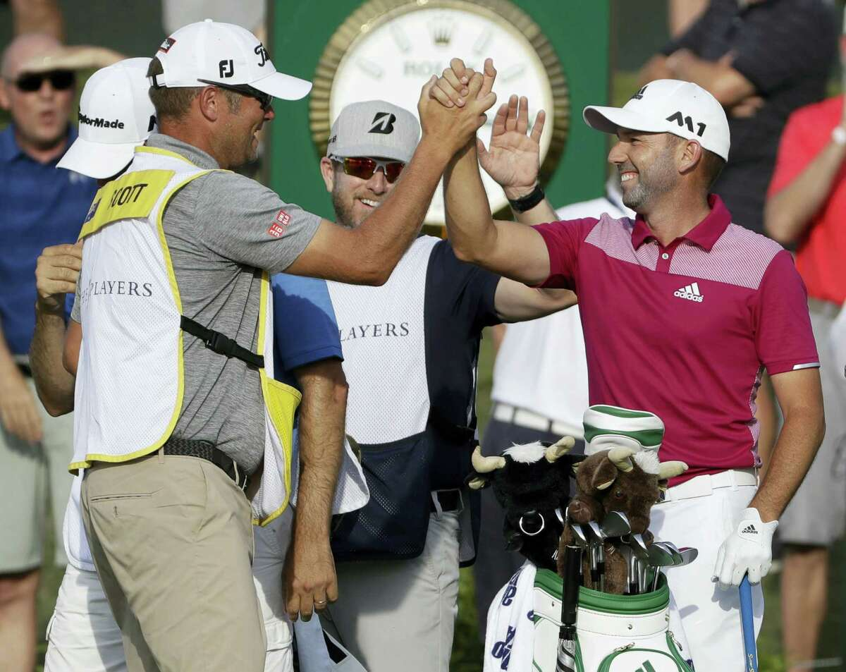 Sergio Garcia, right, is congratulated on the 17th tee after hitting a hole-in-one during the first round of The Players Championship Thursday in Ponte Vedra Beach, Fla.