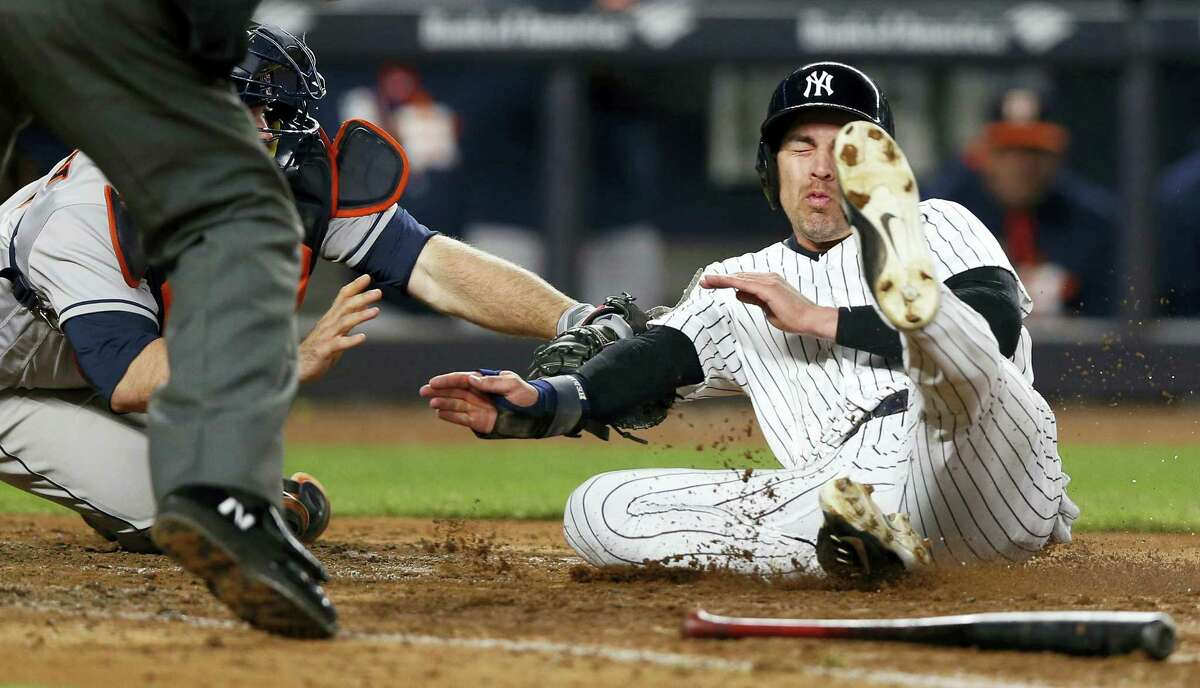 Astros catcher Brian McCann, left, tags out Jacoby Ellsbury at the plate for the final out Thursday.