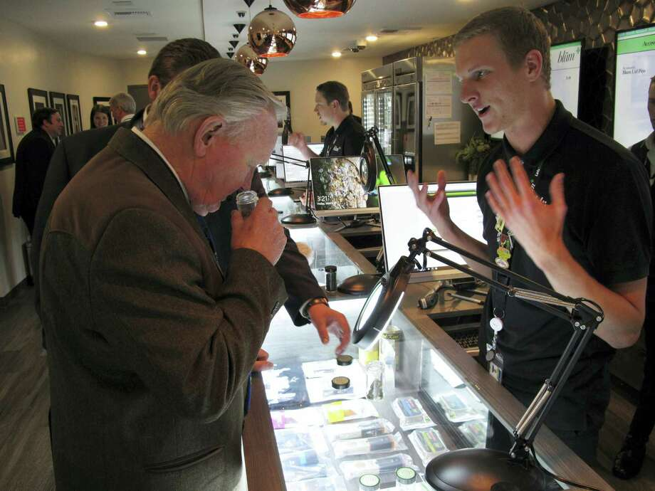 In this March 24, 2017 photo, Nevada state Sen. Don Gustavson, R-Sparks, smells a sample of marijuana as Christopher Price, a ''budtender'' at the Blum medical marijuana dispensary, describes the operation during a brief tour a the store in Reno, Nev. A judge in Nevada is trying to decide whether the state's first sales of recreational marijuana should begin as scheduled July 1 despite complaints from alcohol distributors. Lawyers for the liquor distributors and the Nevada Department of Taxation go before Judge James Wilson in Carson City on June 13, 2017 to argue the case. Photo: AP Photo — Scott Sonner, File   / Copyright 2017 The Associated Press. All rights reserved.