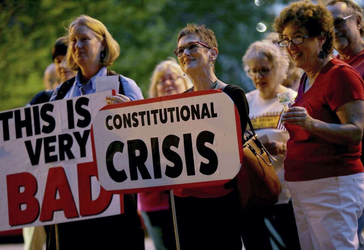 Carol Wofsey, from left, Fran Milsk, and Ellen Bern listen during a vigil to denounce the decision by President Trump to fire FBI Director James Comey outside of the Thomas Eagleton Federal Courthouse in downtown St. Louis, on Wednesday, May 10, 2017. Critics say Trump's focus on possible voter fraud is a ploy to divert attention from his firing of Comey.