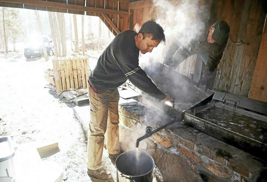 George Page, center, and Doug Williamson drain the reduced maple syrup from a pan into a pot for further reduction in the Sugar Cabin at the Dudley Farm Museum in Guilford on Feb. 4, 2017. Photo: Arnold Gold — New Haven Register