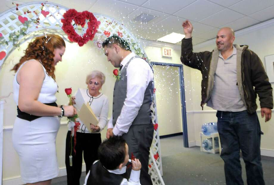 The Hamden Government Center was the location for free Valentine's Day weddings Feb. 14, 2014. Mayra Magana and Felix Barrero (with son Isaac, age 2) tied the knot with the help of Justice of the Peace Myra Rochow and Mayra's father Alfonso Magana throwing confetti. Photo: Mara Lavitt - New Haven Register File Photo   / Mara Lavitt