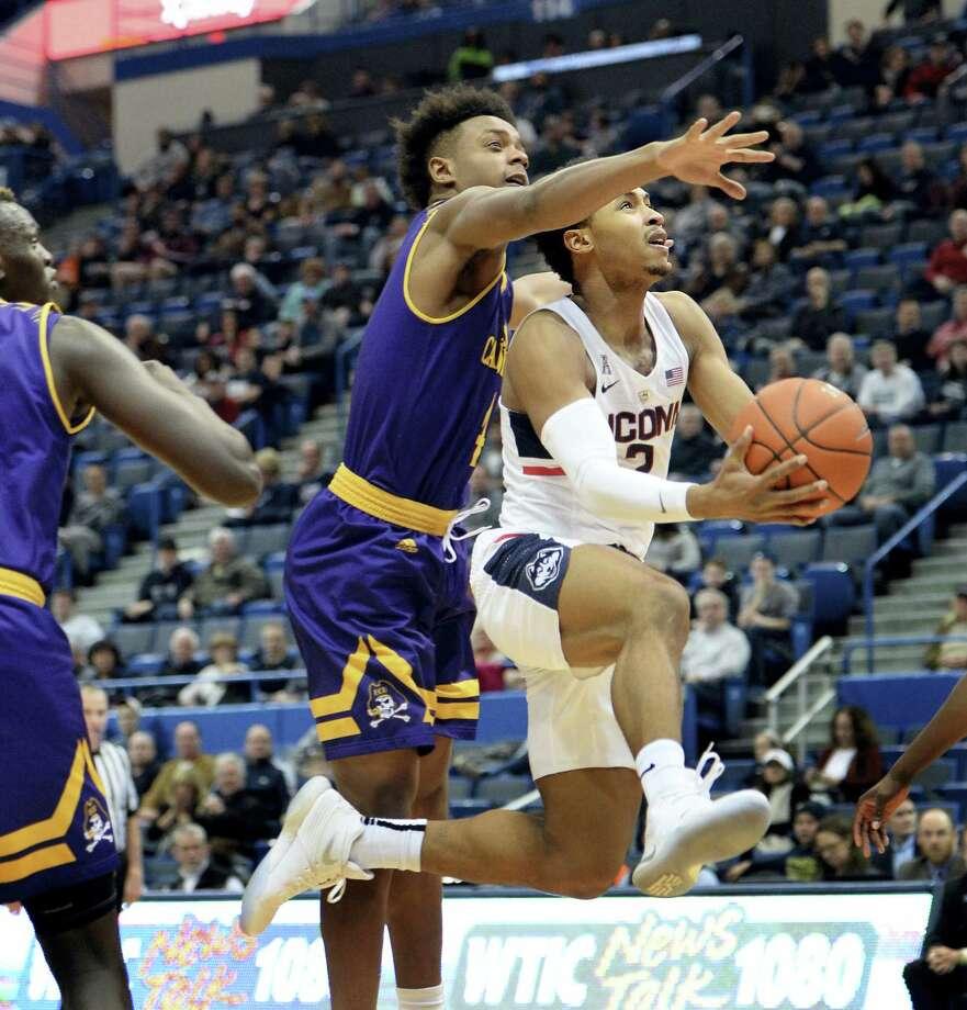 UConn's Jalen Adams (2) is defended by East Carolina's Elijah Hughes during Sunday's game. Photo: Stephen Dunn — The Associated Press   / FR171426 AP