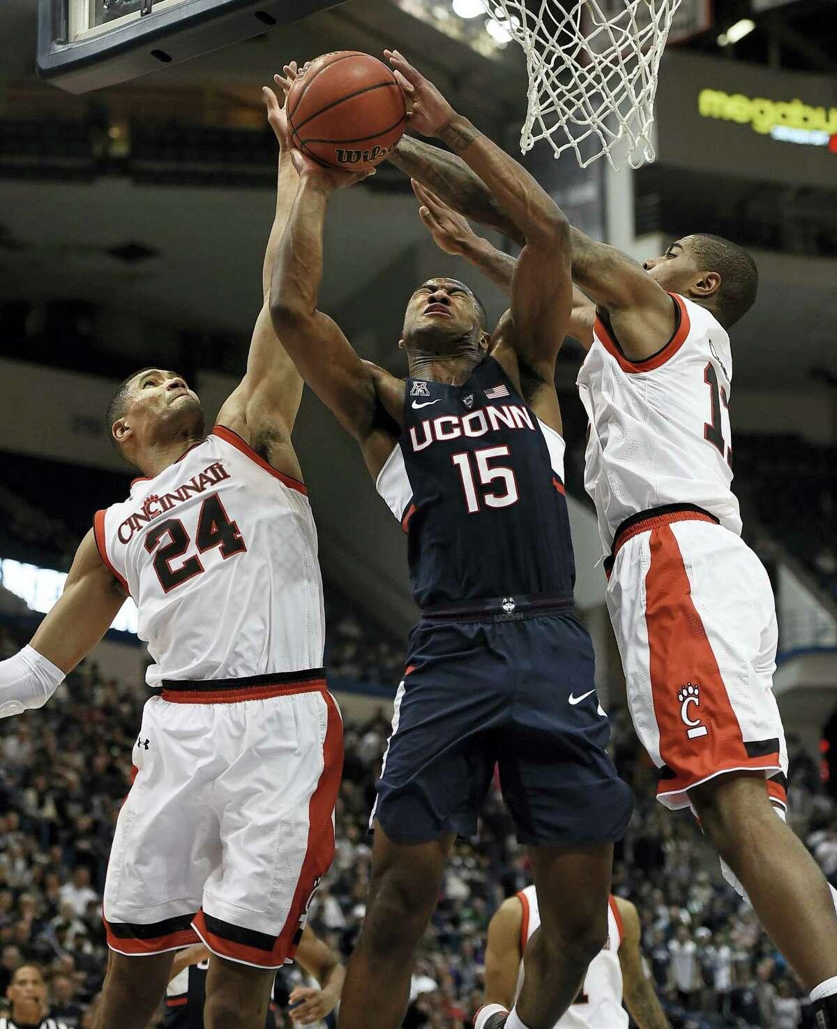 Cincinnati's Kyle Washington, left, fouls UConn's Rodney Purvis during the second half.