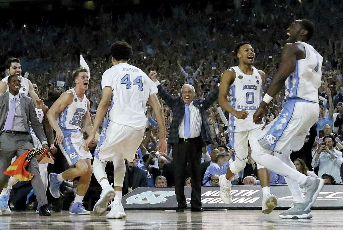 North Carolina head coach Roy Williams and players celebrate after beating Gonzaga to win the national championship Monday Glendale, Ariz. North Carolina won 71-65.