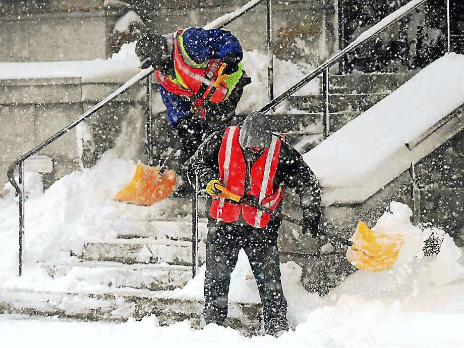 Workers shovel out snow at Yale University's Woolsey Hall in New Haven during the nor'easter snowstorm that swept throughout the city Thursday. Photo: (Peter Hvizdak — New Haven Register)