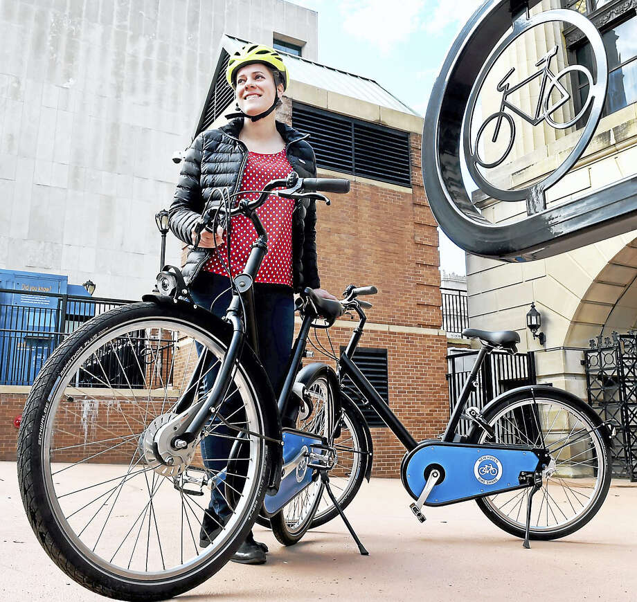 Krysia Solheim, a sustainable consultant for the New Haven Department of Transportation, Traffic and Parking, shows a bicycle outside of the New Haven Hall of Records that may be used for a New Haven Bike Share program. The bike has automatic lights, a GPS, a bell and a Bluetooth smart lock system. Photo: Peter Hvizdak — New Haven Register   / ©2017 Peter Hvizdak