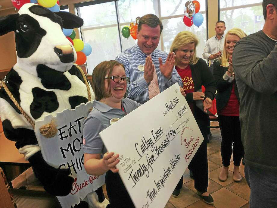 Caitlyn Evans of Cheshire holds a giant replica of a $25,000 check she received Thursday after being chosen as one of 12 Chik-fil-A employees around the country to receive the company's True Inspiration Scholarship. Todd Langston, Evans' boss and owner of the Wallingford location of the fast food restaurant, applauds at right. Photo: LUTHER TURMELLE — NEW HAVEN REGISTER