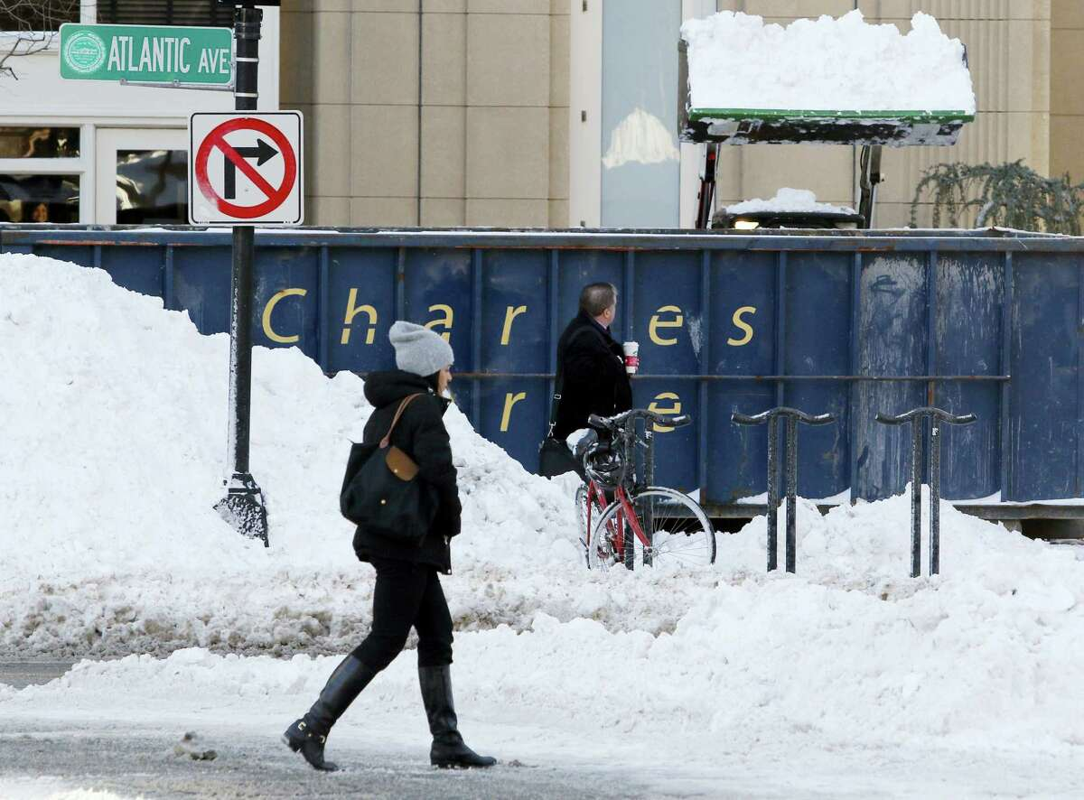 Pedestrians walk past a snow clearing operation, Friday, Feb. 10, 2017, in Boston after the previous day's snowstorm.