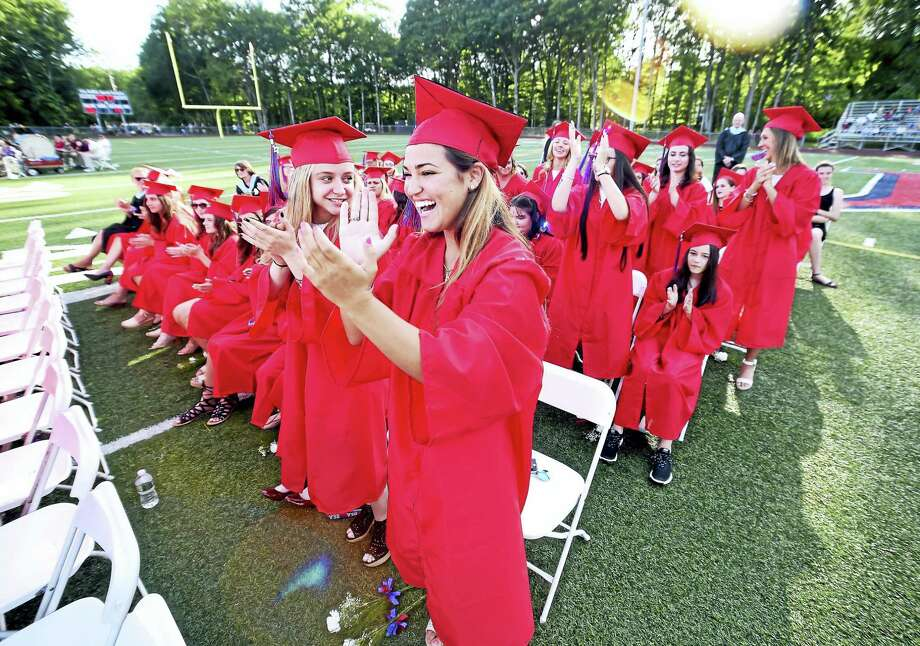 Amanda Mendillo, center, cheers for one of her classmates as diplomas are handed out during the Joseph A. Foran High School commencement Wednesday in Milford. Photo: Arnold Gold/Hearst Connecticut Media