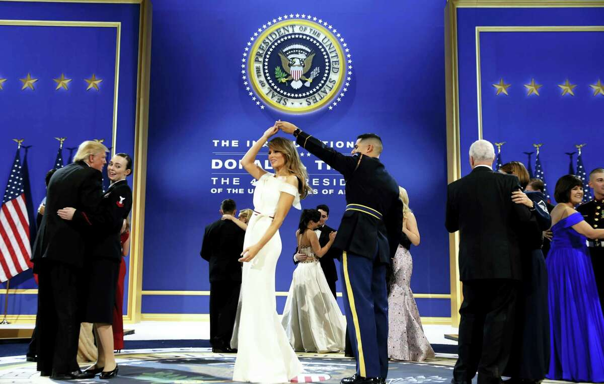President Donald Trump, left, dances with Navy Petty Officer 2nd Class Catherine Cartmell as first lady Melania Trump is spun by Army Staff Sgt. Jose A. Medina during a dance at The Salute To Our Armed Services Inaugural Ball in Washington, Friday, Jan. 20, 2017.