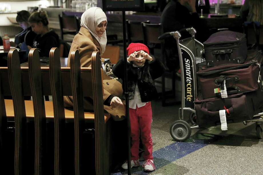 Standing next to her mother, Samar Alwahiri, 3-year-old Laila Alamri, of Yemen, tries to make a heart shape with her fingers at Los Angeles International Airport Wednesday in Los Angeles. More than two dozen Yemenis who were stranded in Africa by President Donald Trump's travel ban arrived Wednesday in Los Angeles. Photo: Jae C. Hong — THE ASSOCIATED PRESS   / Copyright 2017 The Associated Press. All rights reserved.
