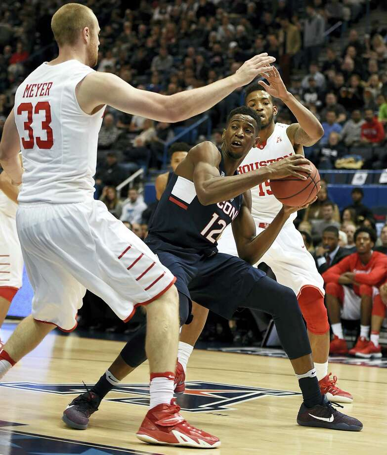 UConn's Kentan Facey, center, looks to pass around Houston's Kyle Meyer, left, and Devin Davis on Friday. Photo: Jessica Hill — The Associated Press   / AP2017