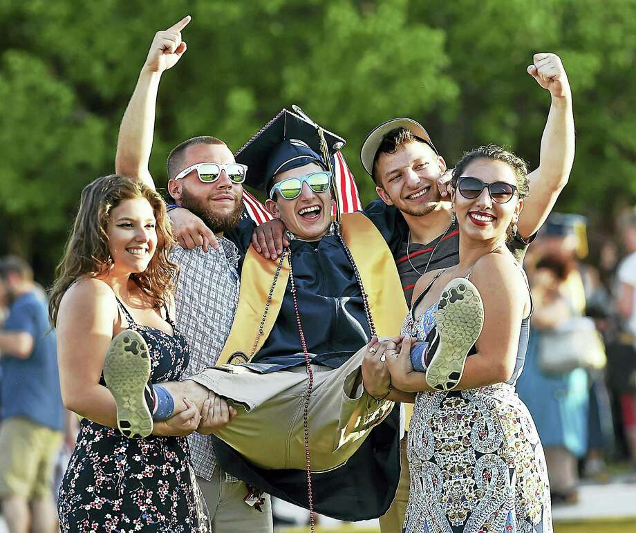 East Haven High School graduate Joe Milano, center,  celebrates with, from left, his sister, Angie Milano; cousin, Lou Dolceacqua; brother Anthony Milano; and aunt Catherine Velazquez following graduation Wednesday. Milano will enter the Marine Corps. Photo: Catherine Avalone/Hearst Connecticut Media   / Catherine Avalone/New Haven Register
