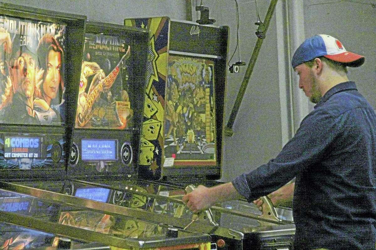 Hamden resident John Esposito plays Demolition Man, a pinball machine located at The Sanctum, a pinball cooperative at 290 Pratt Street, Meriden.