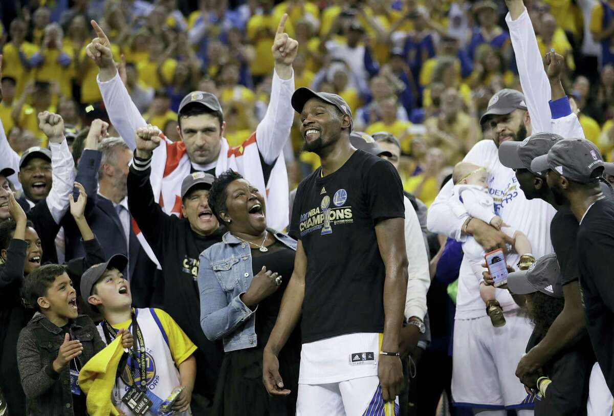 Golden State Warriors forward Kevin Durant, center, celebrates with his mother Wanda Durant as he is named the NBA Finals Most Valuable Player after Game 5 of basketball's NBA Finals between the Warriors and the Cleveland Cavaliers in Oakland, Calif., Monday, June 12, 2017. The Warriors won 129-120 to win the NBA championship. (AP Photo/Marcio Jose Sanchez)