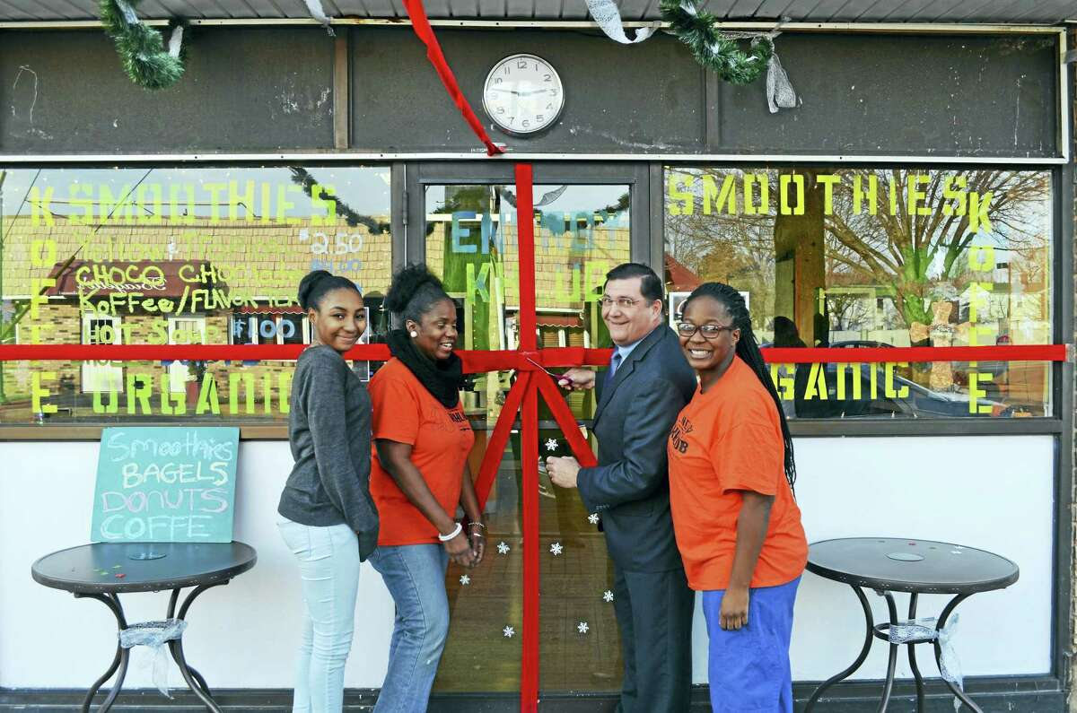 """ENERGY KHLUB: West Haven Mayor Edward M. O'Brien cuts the ribbon Jan. 5 with Energy Khlub owner Mahogany Mathis, right, and her mother, Knia Mathis, second from left, and her sister, Malaizja Mathis, to mark the organic beverage shop's ceremonial opening at 82 Campbell Ave. """"West Haven's new healthy drink shop"""" blends a clever concoction of smoothies — raspberry jungle milk, sweet potato pie, vanilla lime zest — with such staples as coffee, tea, apple cider and hot chocolate. The lower Campbell Avenue business, owned and operated by the Mathis family, also whips up fresh bagels, cake, cookies, soup and doughnuts. The Energy Khlub is open weekdays from 8 a.m. to 6 p.m. and Saturdays from 8:30 a.m. to 6 p.m."""