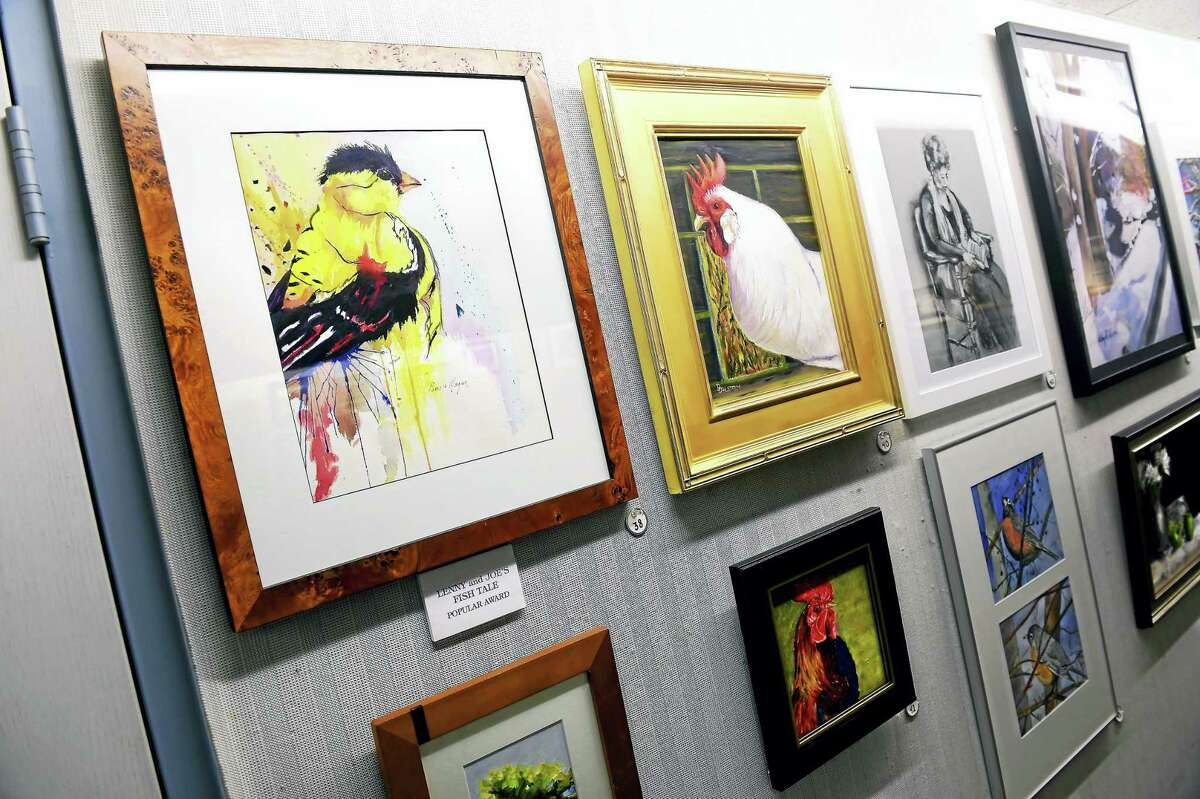 """""""The Goldfinch,"""" far left, a watercolor painting by Pamela Morgan, is displayed with the 42nd annual Madison Art Society Member Exhibition in the Community Room of the E.C. Scranton Memorial Library in Madison."""