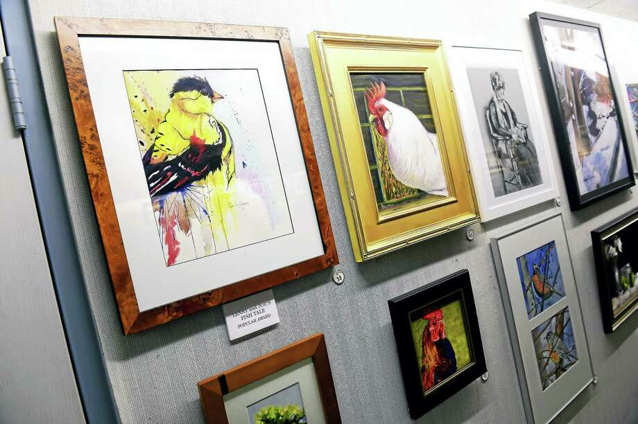 """""""The Goldfinch,"""" far left, a watercolor painting by Pamela Morgan, is displayed with the 42nd annual Madison Art Society Member Exhibition in the Community Room of the E.C. Scranton Memorial Library in Madison. Photo: Arnold Gold — New Haven Register"""