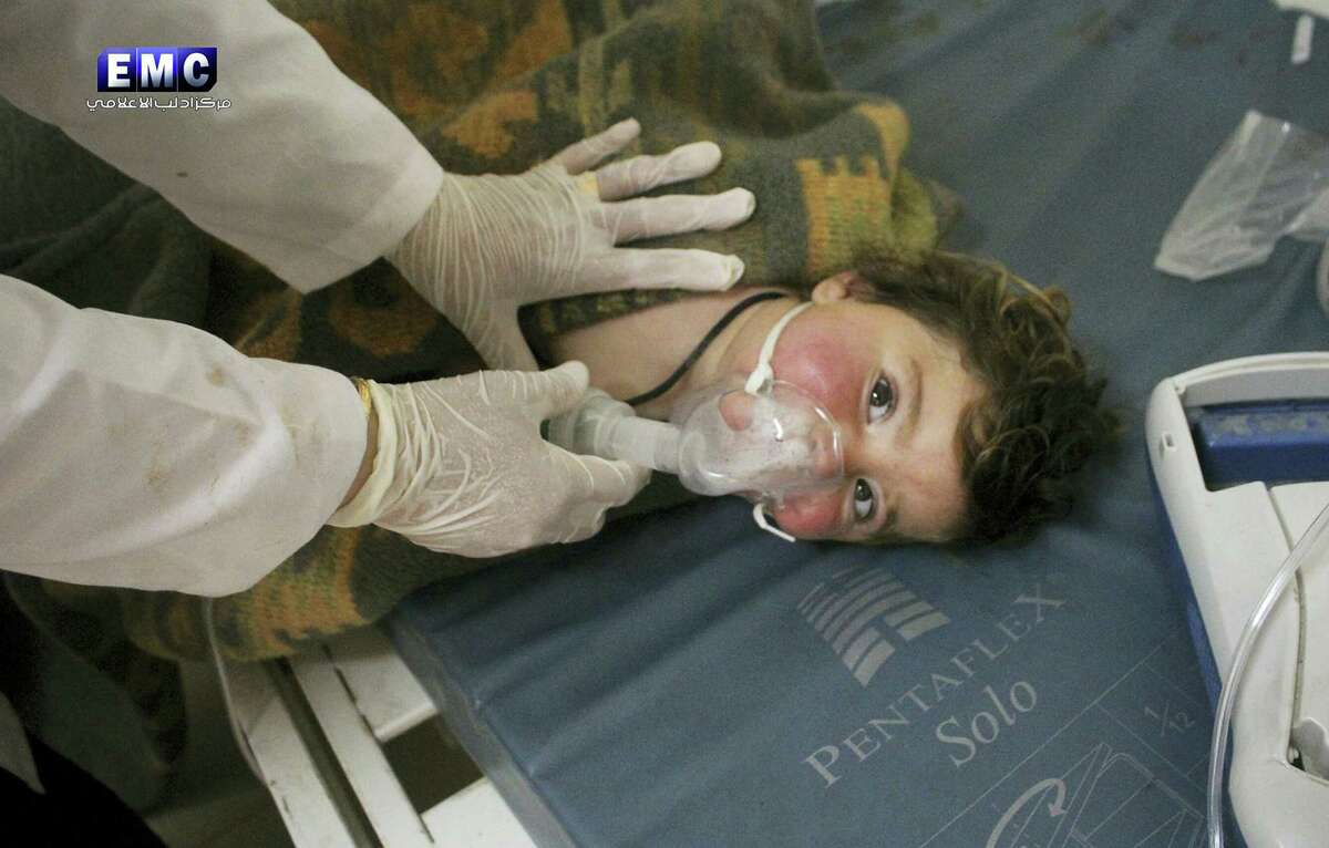 This photo provided April 4, 2017 by the Syrian anti-government activist group Edlib Media Center, which has been authenticated based on its contents and other AP reporting, shows a Syrian doctor treating a child following a suspected chemical attack, at a makeshift hospital, in the town of Khan Sheikhoun, northern Idlib province, Syria. The suspected chemical attack killed dozens of people on Tuesday, Syrian opposition activists said, describing the attack as among the worst in the country's six-year civil war.