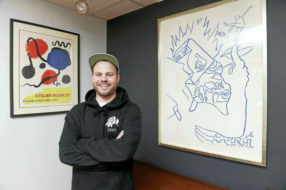 Justin Norman between a Mark Kostabi original crayon drawing, right, and an Alexander Calder poster, left, at his store, CT Modern, on Main Street in Branford. Photo: Arnold Gold — New Haven Register