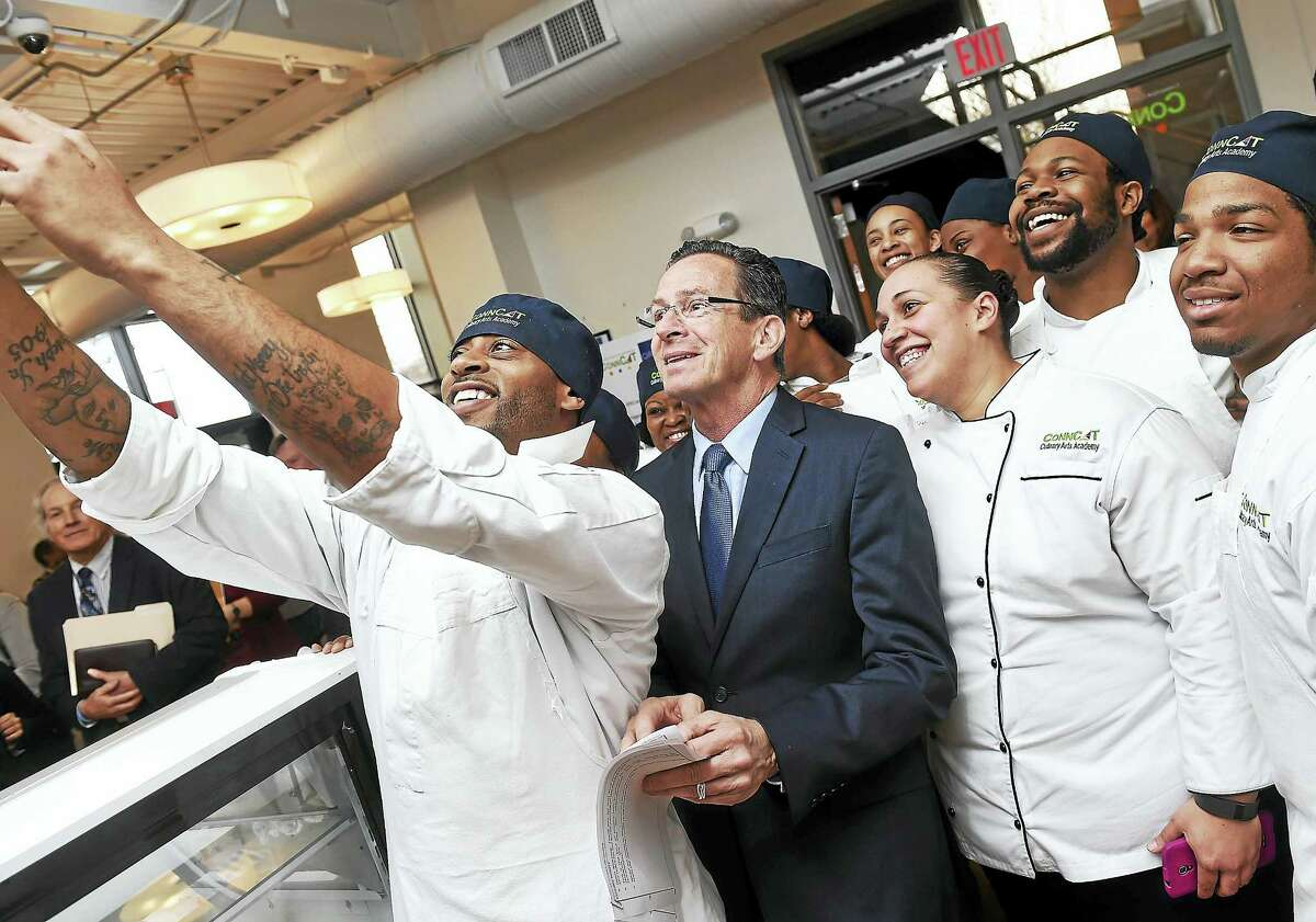 Joseph Williams, left, and other culinary students at ConnCAT's Orchid Cafe take part in a selfie with Gov. Dannel Malloy, center, during the grand opening Tuesday in New Haven.