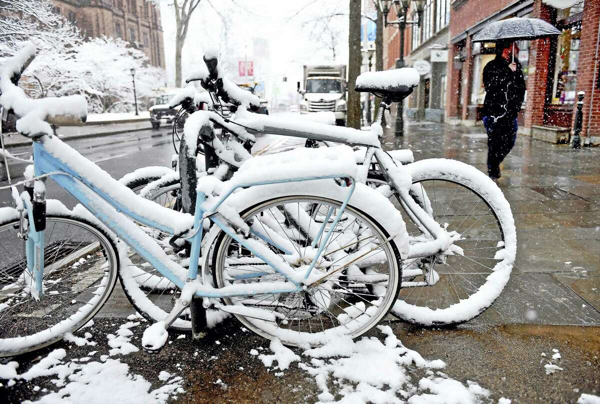 Snow sticks to bicycles but not to the sidewalk on Chapel St. in New Haven on Friday.