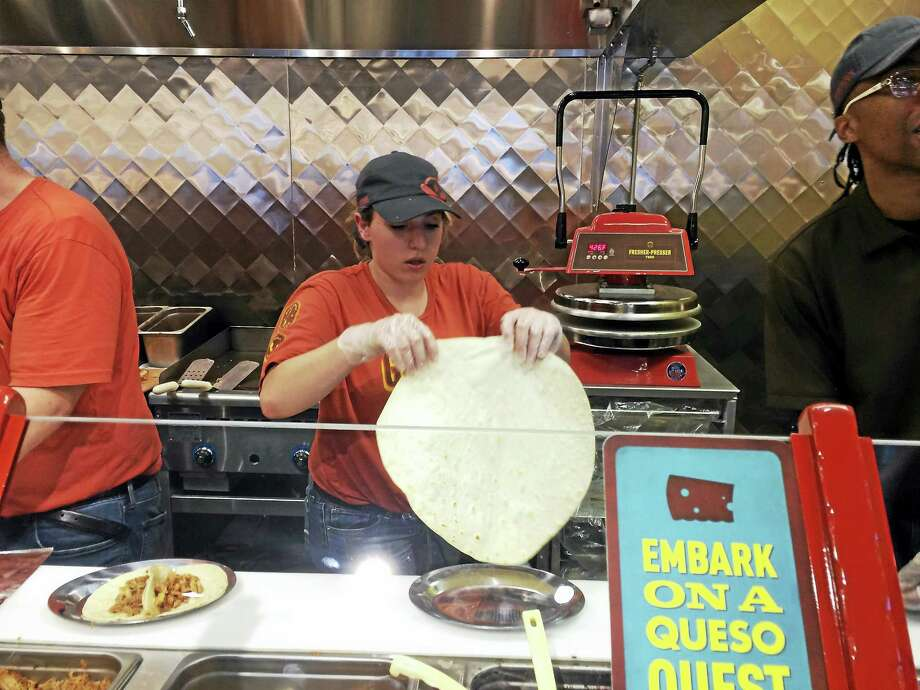A Pancheros Mexican Grill worker prepares a freshly made burrito at the restaurant chain's new Wallingford location, which opened for business Tuesday. Photo: LUTHER TURMELLE — NEW HAVEN REGISTER
