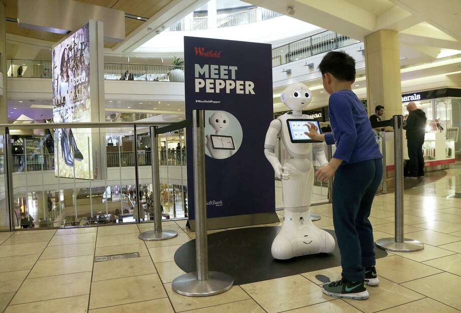 A boy plays with Pepper the robot at Westfield Mall in San Francisco. While merrily chirping, dancing and posing for selfies, Pepper looks like another expensive toy in the San Francisco mall where it will be entertaining shoppers through mid-February. But it would be a mistake to dismiss Pepper as mere child's play, even though kids flock around the 4-foot-tall humanoid as it speaks in a cherubic voice that could belong to either a boy or girl. Photo: Jeff Chiu — The Associated Press   / Copyright 2016 The Associated Press. All rights reserved.