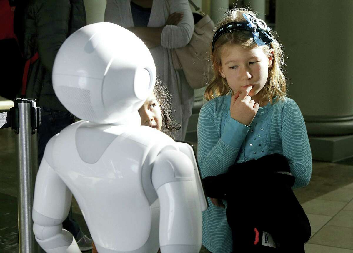 Emerson Hill, 6, plays with Pepper the robot at Westfield Mall in San Francisco.